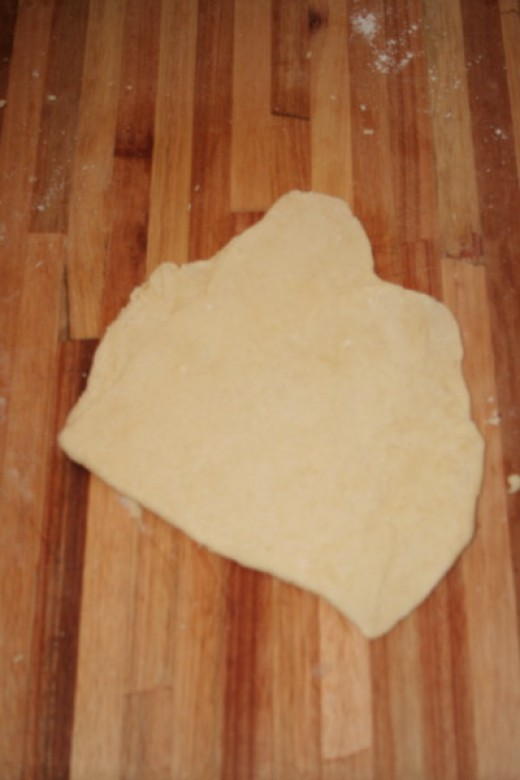 Pastry dough being rolled out, folded in half and rolled out again