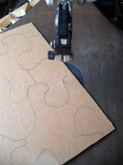 Use a scroll saw to cut the puzzle in to pieces.