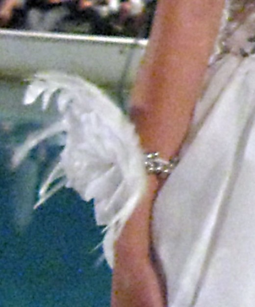 Feathers on a bracelet worn as part of a wedding ensemble.