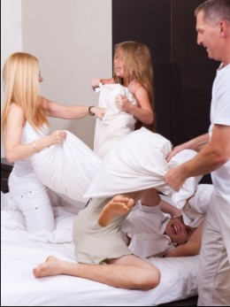Happy Family Having A Pillow Fight by photostock