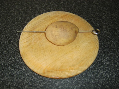 Metal skewer is carefully inserted lengthwise through the centre of the raw potato