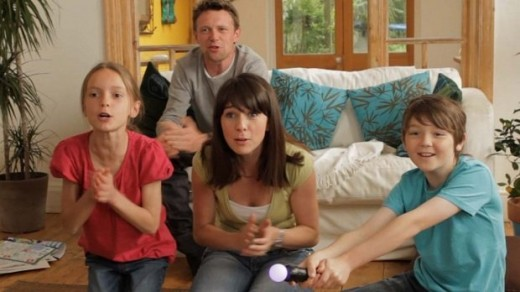 A family playing a PS3 Move game together