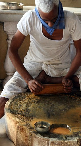 A villager making sandalwood paste in a Lord Shiva temple..