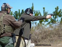 Firearms instructor working with student.