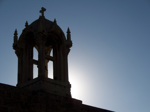 The sun sets behind an old church steeple, Lebanon