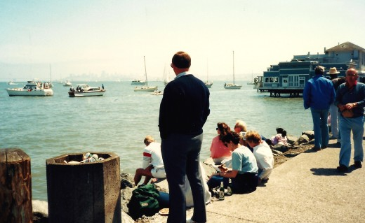 Water view from Sausalito - People eating pizza by the slice; ice cream cones, etc. while sitting on the rocks and sidewalk watching the different boats on the water.