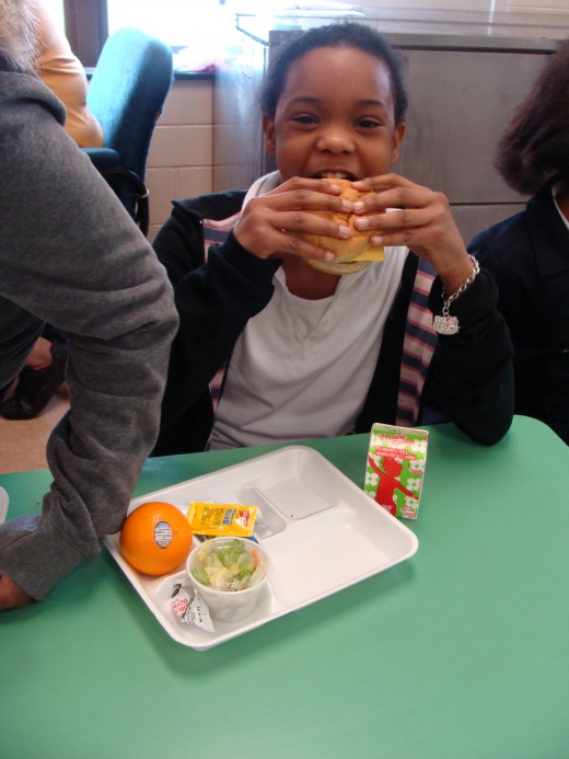 This student's lunch was a mix of high and low quality food.  The processed hamburger was served on what appeared to be a whole wheat bun and lettuce, with an orange and strawberry flavored milk.