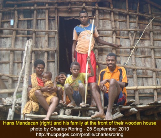 The indigenous Papuan people In Arfak mountains posed in front of their wooden house
