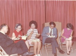 Part of a group eating in the church fellowship hall. They have selected their own seats.
