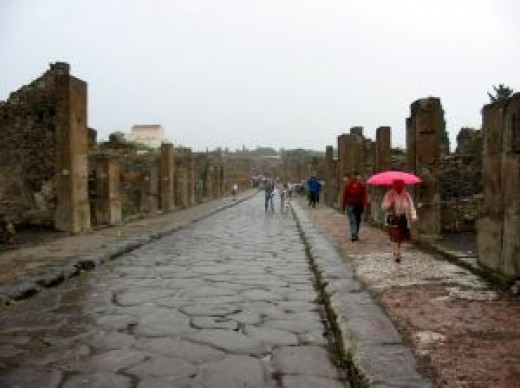 Tourists walk along a street in the ruined city.