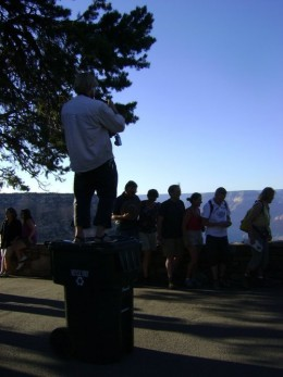 Tourist standing on a garbage can.