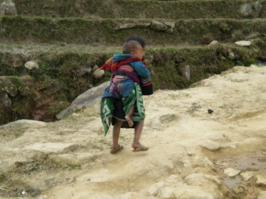 Hill Tribe Vietnamese Girl carrying a baby, Hoang Lien Mountains, Sapa, Vietnam.