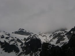 More clouds and a cold wind. See the black rock cliffs below the upper glacier.