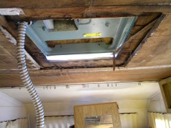 With the AC ceiling assembly and hold-down bracket removed, the damaged ceiling is ready to be removed and replaced.