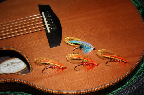 "This photo shows my four salmon fly brooch pins (top fly-""Blue Breeze""; bottom three are all called ""Sunset""), against  the body of my McPherson MG-3.5 acoustic guitar."