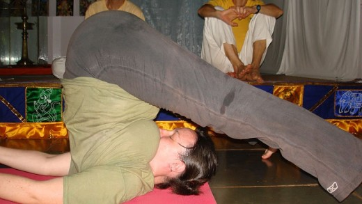 A girl doing halasana yoga pose in a yoga training center in Delhi.