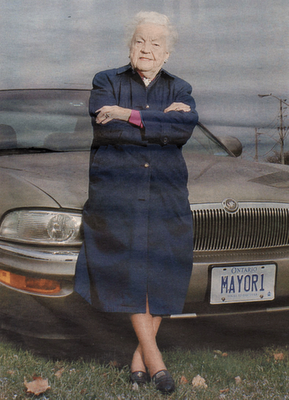 Hazel in front of her car with her personalized license plate