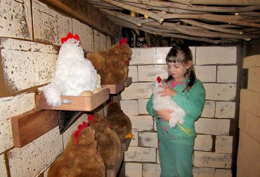 a girl playing in the chicken coop. she's touching a stuffed chicken animal.