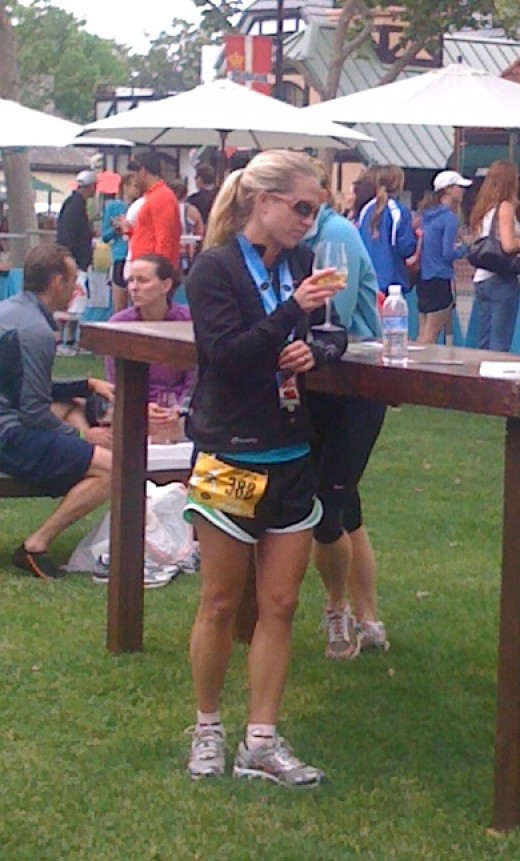 A racer re-hydrates and celebrates with some wine after a wine country half marathon