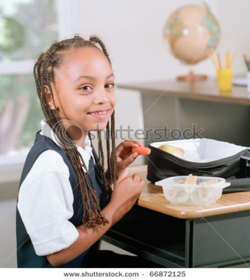 Girl eating lunch at her desk.