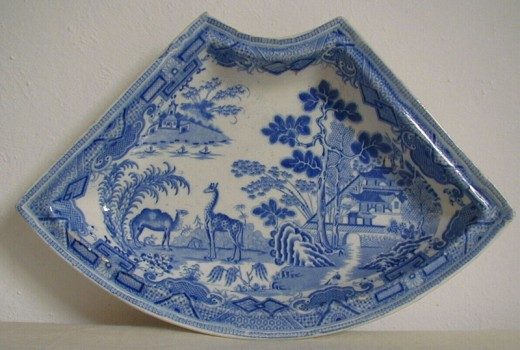 Section of a Minton pearlware supper dish C1812: The giraffe in this Minton pattern, introduced C1812, is oddly flat-footed, bearing a pronounced hump above his shoulder, and is barely distinguishable from his camel companion seen to the left.