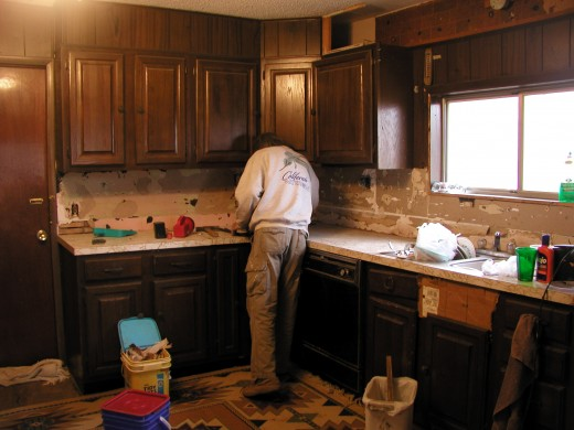 """Al starting to dismantle the old kitchen..MY Favorite part!  I love tearing old stuff out!  The cabinets look """"ok"""" in this pic but, believe me, they were not!"""