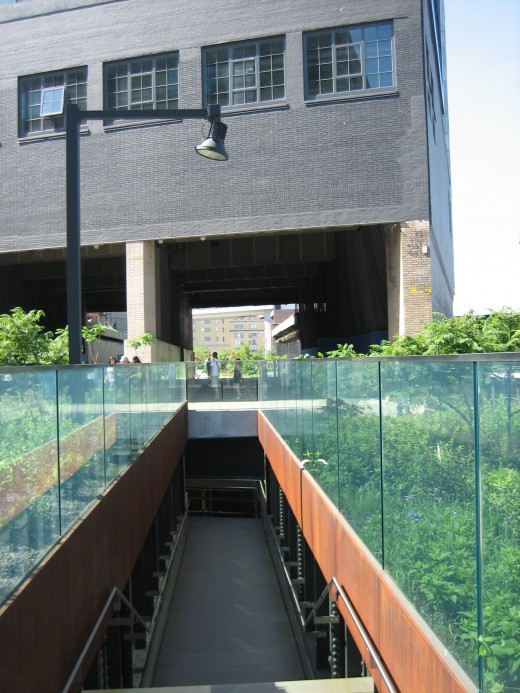 A stairway to the street, and a building through which the High Line passes. Inside, there's a public art installation