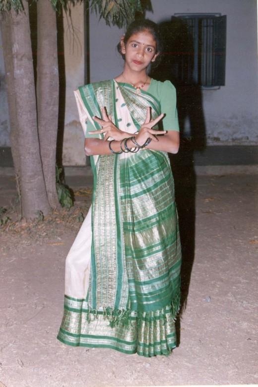 A teenage girl in agrand saree( observe the silver coloured designs on the pallu and border.Body of sari has creamy colour and plain)