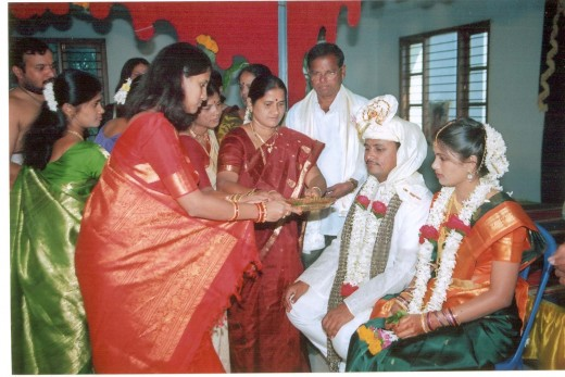 A scene from a south Indian hindu wedding.(observe the grand designs on the red saree ofthe greeting lady)