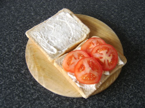 The chicken is laid on one slice of the bread with the tomato on top