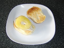The chicken breast is halved and placed on one half of the roll with the pineapple ring