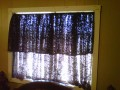 ( WINDOW) A spring rod is placed inside window.A chocolate lace fabric is draped across the rod for the window cover. now if you drap it from the back side it will give your window a double treatment without the sewing