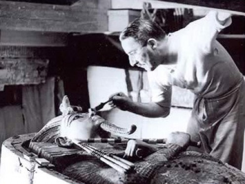 Howard Carter gently brushes dust from the sarcophagus of King Tut.