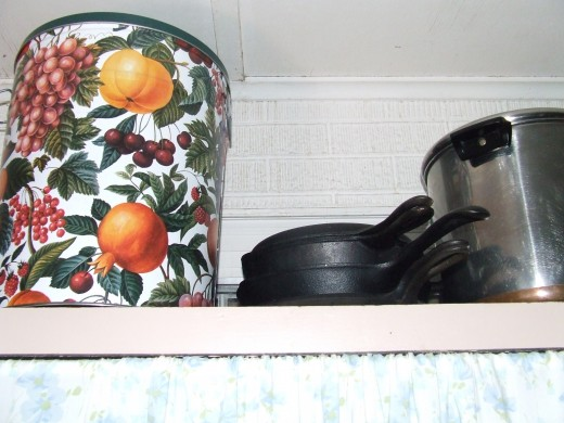 I keep all paper plates, napkins and plastic ware in the tin with the fruit pattern,  for summer time use.  I also keep extra  cookware next to the tin.