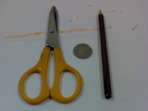 a pair of scissors, a coin, pencil..