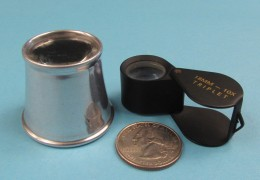 (Fig 1) Two typical loupes with quarter shown for size comparison. Style on left is a watchmakers loupe; folding style, right, is a jewelers loupe.