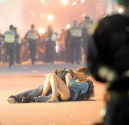 These two had just exited the Roger's Arena when mistaken by the police for rioters. She was knocked to the ground and he proceeded to comfort her from the shock of police attack. They were not rioters. He is a tourist! The story has gone viral.