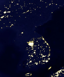 """""""An image of the Korean Peninsula at night rendered from DMSP observations. The disparity in illumination levels is an indication of the difference in population and energy between the North and South"""""""