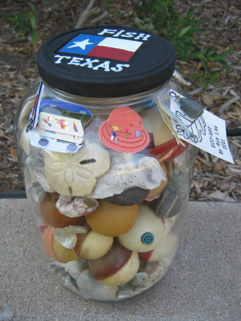 Jar full of seashells and fishing bobbers I've found over time.To complete the fishing theme, I painted the lid and tied some fishing related trinkets around the neck of the jar. All items I already  had.