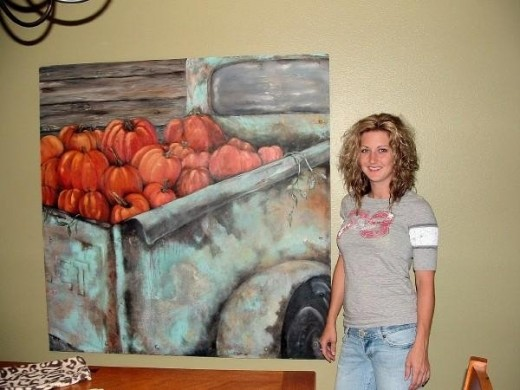 This is Nikki Garrett standing beside one of her paintings.  This one is a 4' x 4' acrylic painting on sheet metal of a truck load of pumpkins.  You can see that Nikki is as beautiful as the art she creates.
