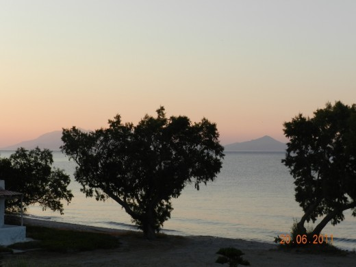Sunrise coloring the surrounding islands and trees in tones of pink and orange