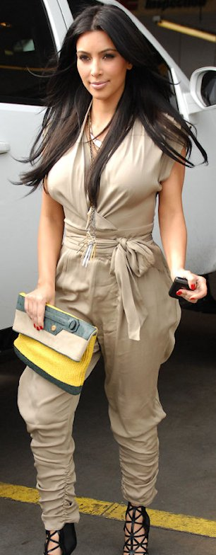 Kim Kardashian wearing a sexy jumpsuit and carrying a peppy yellow clutch.