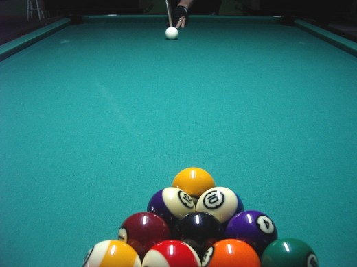 Photo 5: A player about to break in the centre of the table, from behind the head-line.  The worn marks caused by the most normal breaking positions are visible on the baize.