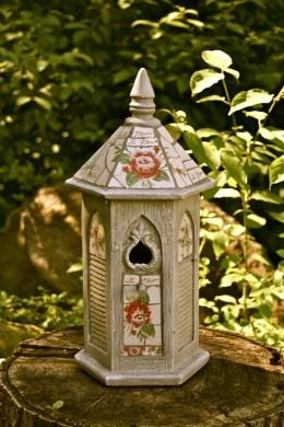 A birdhouse sitting on a short tree stump.