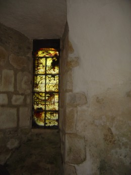 The chapel is lit by a small window with stained glass.