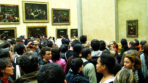 Crowds dwarf the Mona Lisa on the right.