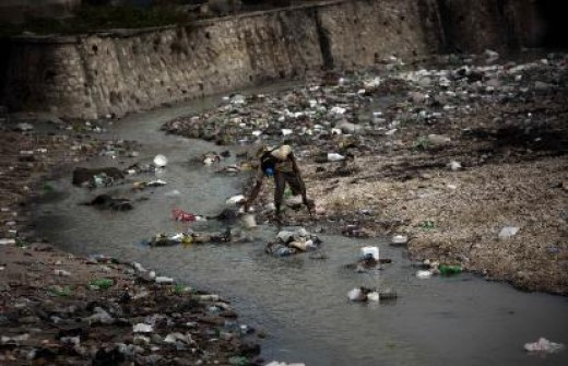 A man collects water in a river covered with waste in Port-au-Prince, Haiti, on Friday. AP photo