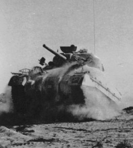 M4 Sherman Tank Fighting in North Africa. This American made tank armed with a 75mm cannon gave the allies parity against the German Panzers of the Afrika Korps.