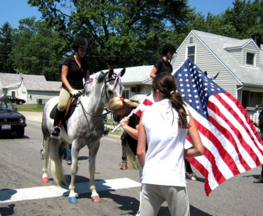 As the parade pauses, nearing the judge's booth, this 5 year old pony gets a well-deserved kiss on the nose from mom. No worries about the flag in her hand, parades are now just another fun day for him!