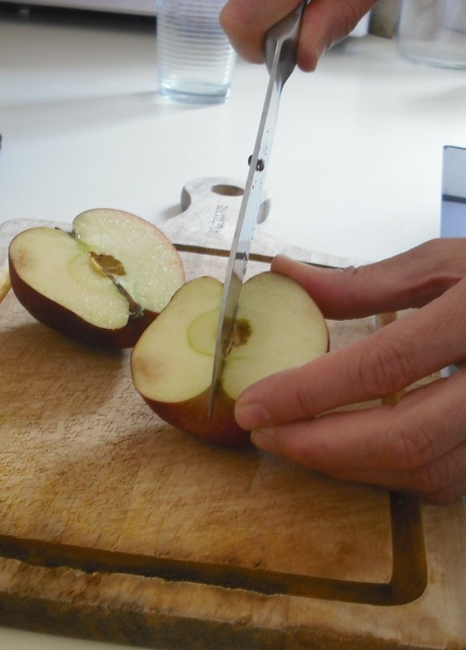 Cut the apple in half. Then cut it into quarters.